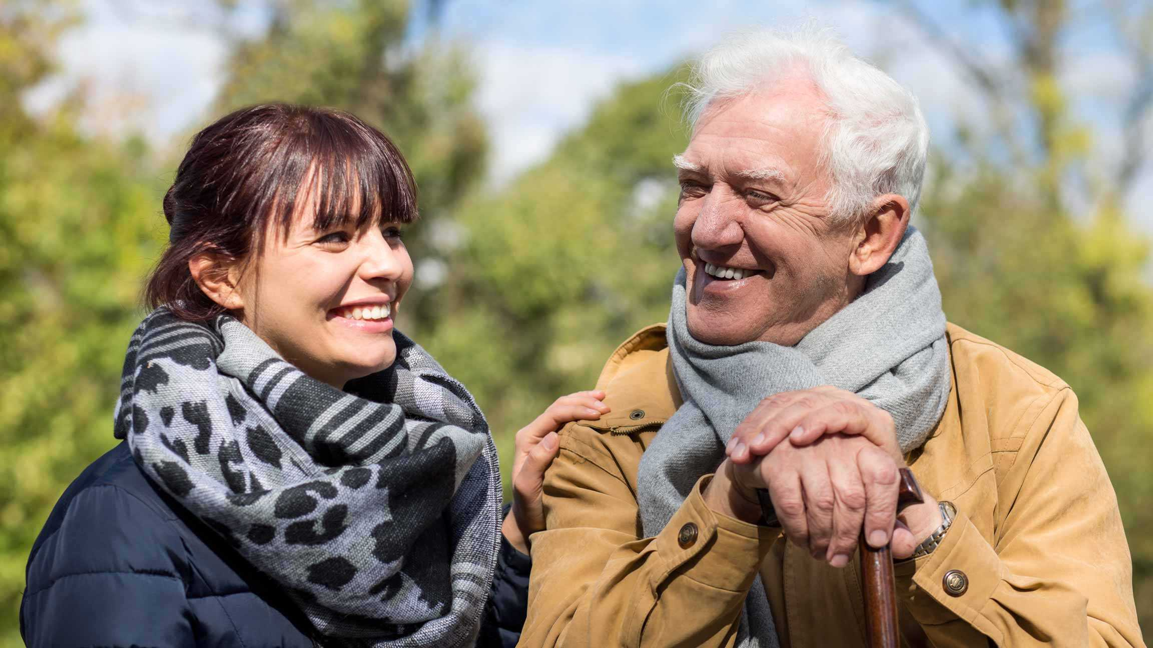 Young female care worker supporting an older man with dementia, who is smiling and has a walking stick