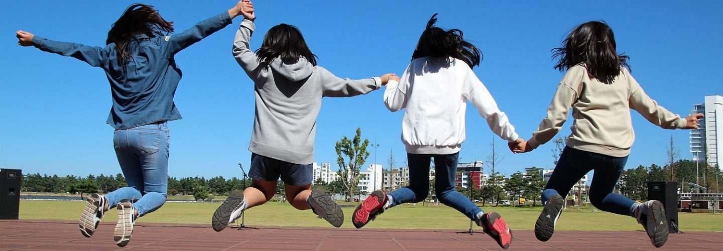 Four girls holding hands and jumping in a playground