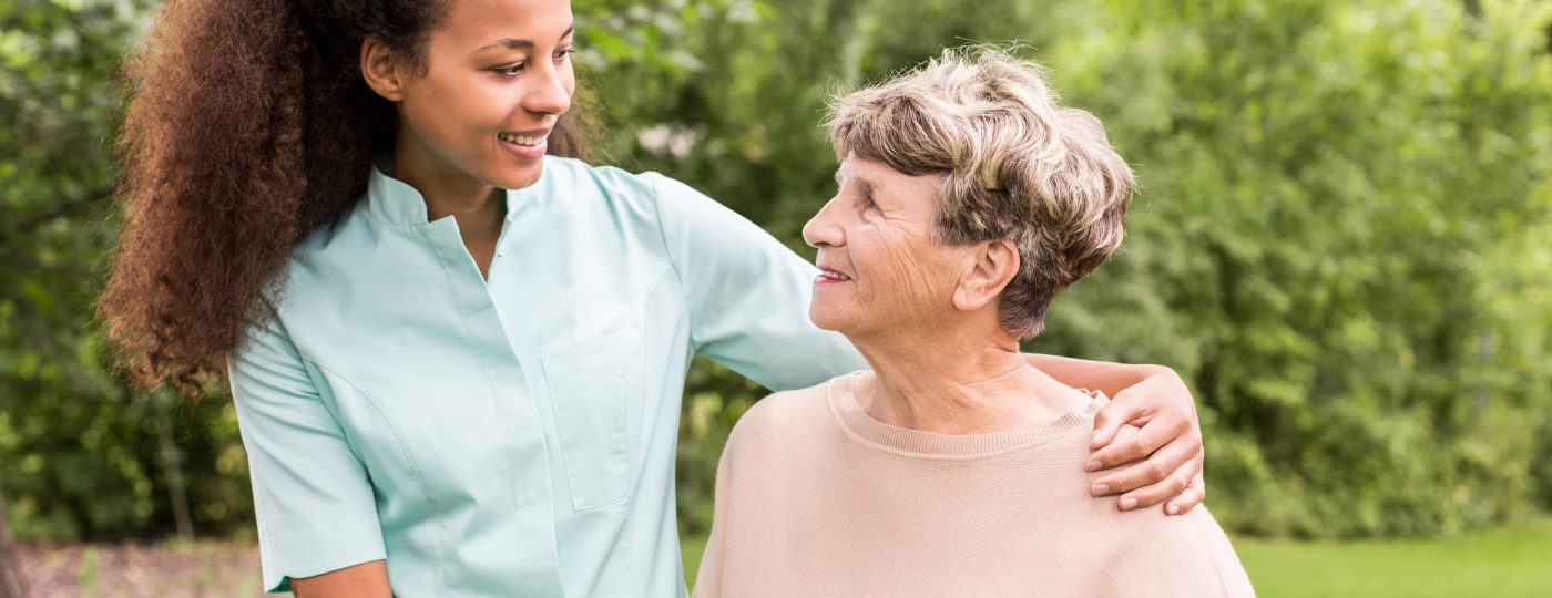 Carer and older lady smiling at each other
